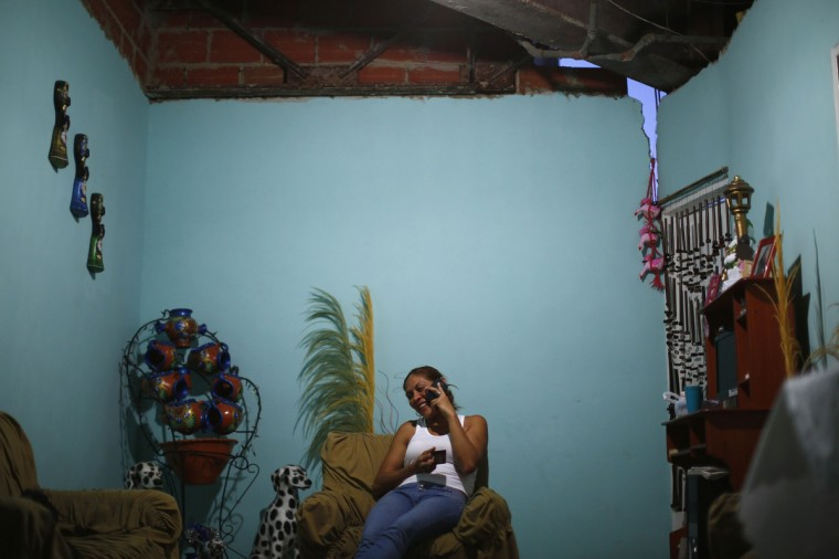 Thais Ruiz, 36, talks on the telephone and drinks coffee as she sits under a crack in the roof of her living room on the 27th floor. (Jorge Silva/Reuters)