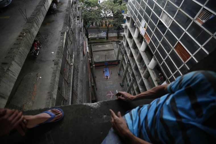 "Men sit and look down at a basketball court inside the ""Tower of David"" skyscraper in Caracas. (Jorge Silva/Reuters)"