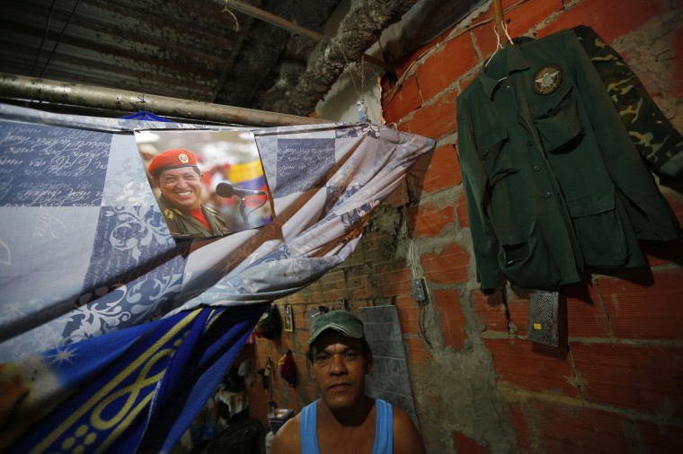 "Jose Aular poses next to a portrait of Venezuela's late President Hugo Chavez in his apartment inside the ""Tower of David"" skyscraper in Caracas. (Jorge Silva/Reuters)"
