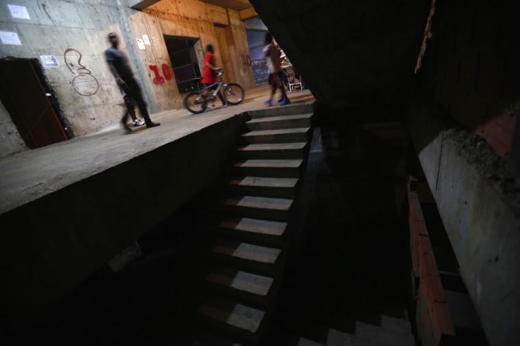 "People walk along a corridor on the 10th floor of the ""Tower of David"" skyscraper in Caracas. (Jorge Silva/Reuters)"