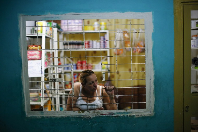 "A woman looks out of a window at her shop in a corridor inside the ""Tower of David"" skyscraper in Caracas. (Jorge Silva/Reuters)"