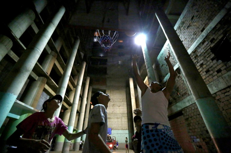 "Boys play basketball in a garage at the ""Tower of David"" skyscraper in Caracas. (Jorge Silva/Reuters)"