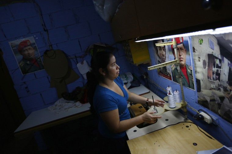 "Maria works in a sewing workshop in her apartment inside the ""Tower of David"" skyscraper. (Jorge Silva/Reuters)"