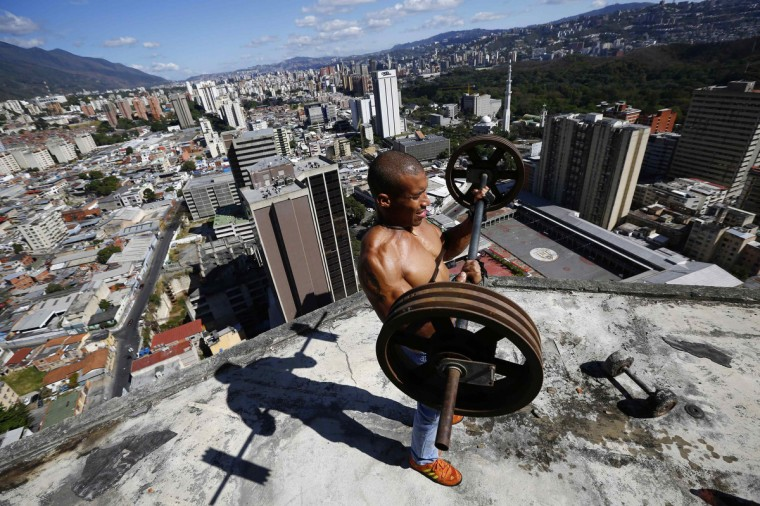 "Gabriel Rivas, 30, lifts weights on a balcony on the 28th floor of the ""Tower of David"" skyscraper in Caracas. (Jorge Silva/Reuters)"