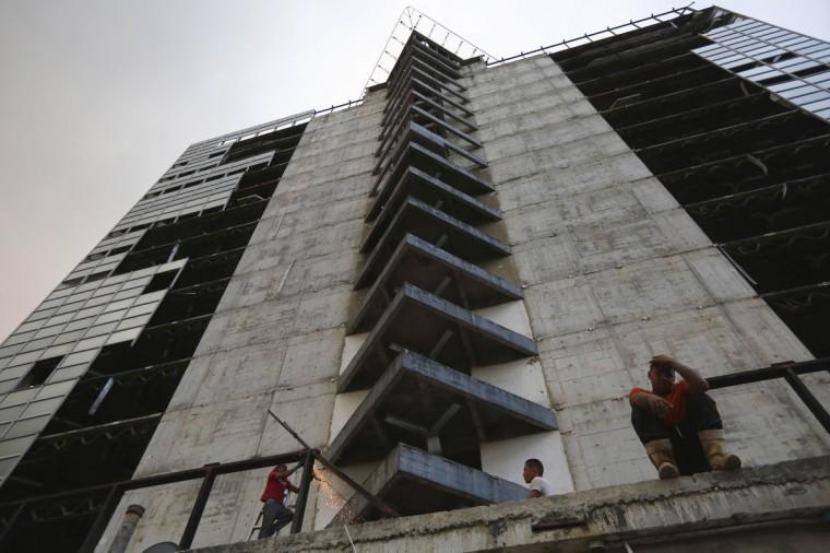 "Men salvage metal on the 30th floor of the ""Tower of David"" skyscraper in Caracas. (Jorge Silva/Reuters)"