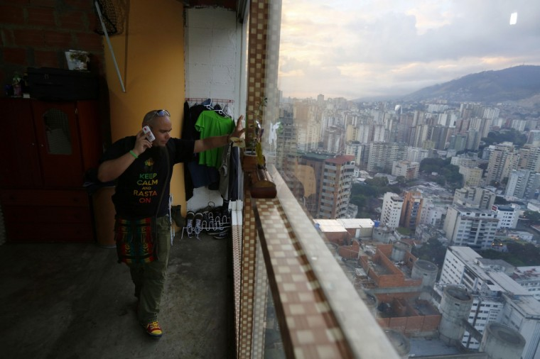 "Nicolas Alvarez speaks on the telephone in his apartment on the 27th floor of the ""Tower of David"" skyscraper. (Jorge Silva/Reuters)"