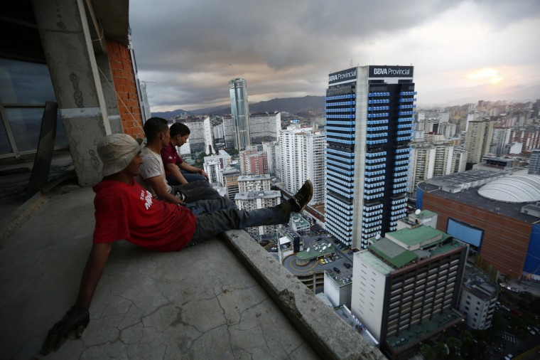"Men rest after salvaging metal on the 30th floor of the ""Tower of David"" skyscraper in Caracas. (Jorge Silva/Reuters)"
