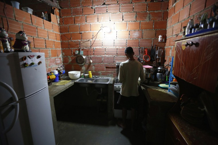 "Francisco, 18, cooks in his apartment inside the ""Tower of David"" skyscraper. (Jorge Silva/Reuters)"