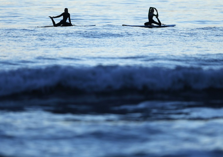 Twelve-year-old certified yoga instructor Jaysea DeVoe (R) does the mermaid pose with her friend Miely as they float on their paddle boards after the sun sets in Encinitas, California March 19. DeVoe is just 12 years old and recently became a certified yoga instructor after completing 200 hours of teacher training. She is believed to be the youngest certified female yoga instructor in the United States. In addition to teaching pint-sized students aged 4 to 6, DeVoe instructs teens and fellow tweens in her California beach town of Encinitas and is about to start a family yoga class. Picture taken March 19, 2014. || PHOTO CREDIT: MIKE BLAKE - REUTERS