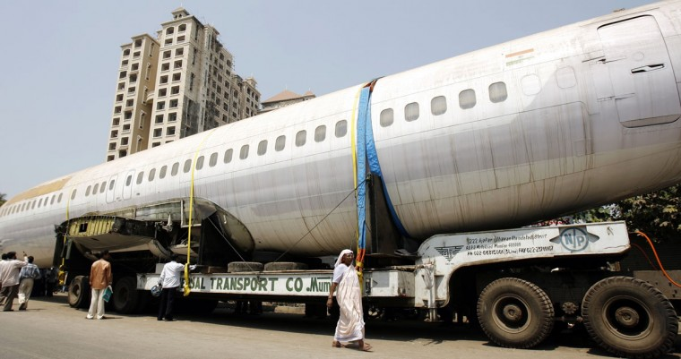People walk past the fuselage of a Boeing 737 parked on a road in Mumbai on May 3, 2007. (REUTERS/Arko Datta)
