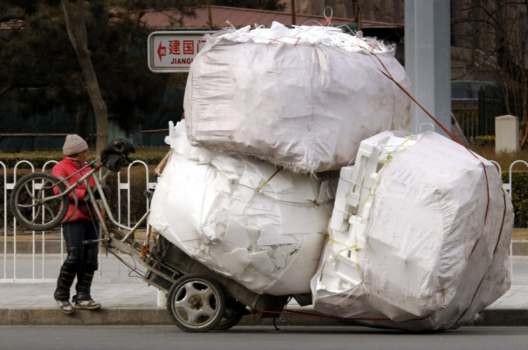 A recyclable materials collector stands in front of her overloaded tricycle on a main street in central Beijing on March 12, 2010. (REUTERS/David Gray)