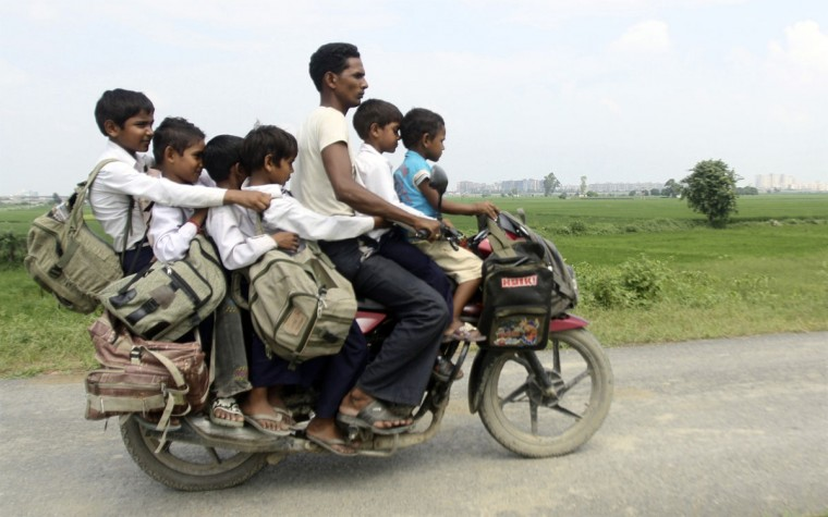 A man rides a motorcycle carrying six children on their way back home from school at Greater Noida in the northern Indian state of Uttar Pradesh on September 10, 2010. (REUTERS/Parivartan Sharma)