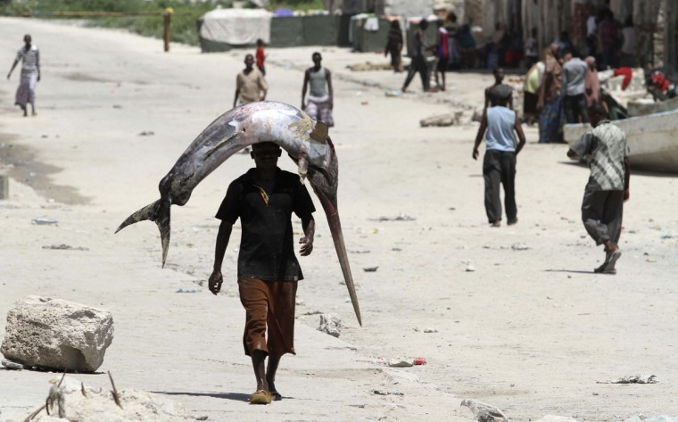 A fisherman carries a fish from the shores of the Indian Ocean in Hamarweyne district, Somalia's capital Mogadishu, on November 4, 2011. (REUTERS/Feisal Omar)