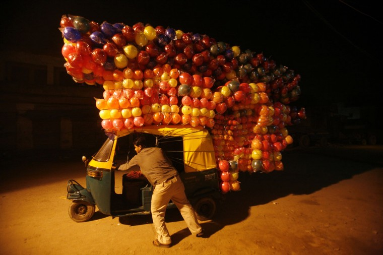 A man pushes an auto-rickshaw loaded with plastic balls to sell at a wholesale market in New Delhi on November 10, 2011. (REUTERS/Parivartan Sharma)