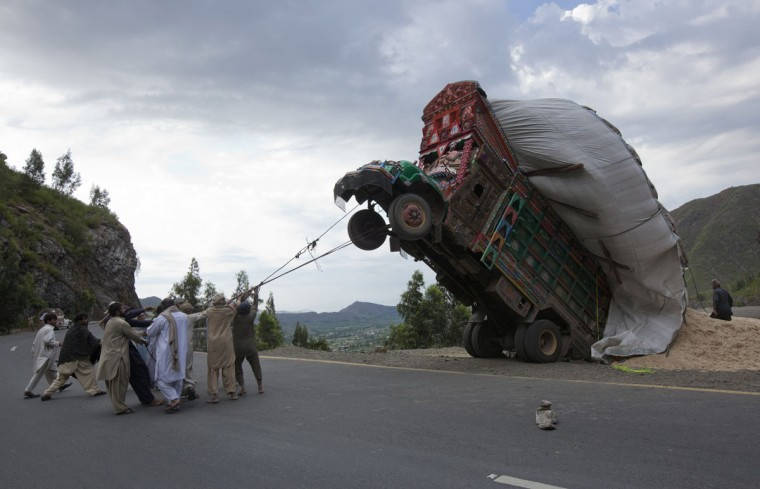 Men use ropes to try and right a supply truck overloaded with wheat straw, used as animal feed, along a road in Dargai, about 100 miles northwest of Pakistan's capital Islamabad, on April 13, 2012. (REUTERS/Mian Khursheed)