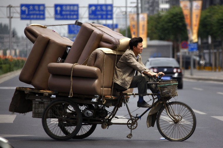 A man rides a tricycle loaded with lounge chairs along a road in Beijing on June 5, 2012. (REUTERS/David Gray)