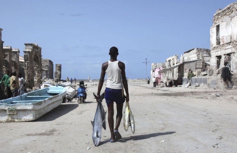 A man carries fishes from the shores of the Indian Ocean in Mogadishu on June 12, 2012. (REUTERS/Ismail Taxta)