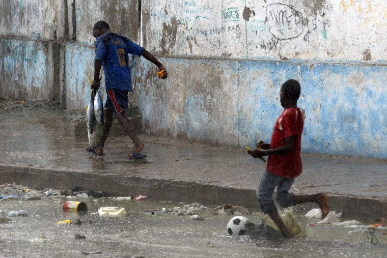 A man carries fish home near a boy playing football in heavy rain in Mogadishu on June 28, 2012. (REUTERS/Goran Tomasevic)