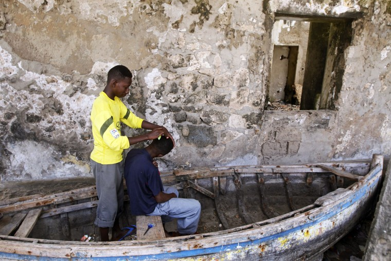 A man trims hair for his friend at a fishermen port destroyed during the war in Mogadishu on June 29, 2012. (REUTERS/Goran Tomasevic)