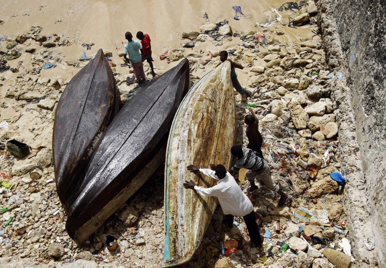 Men work on fishing boat in a fishing port in Mogadishu on June 30, 2012. (REUTERS/Goran Tomasevic)