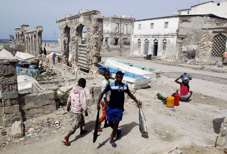 A fisherman carries his catch in front of buildings, destroyed during a war, near a fishing port in Mogadishu on June 30, 2012. (REUTERS/Goran Tomasevic)