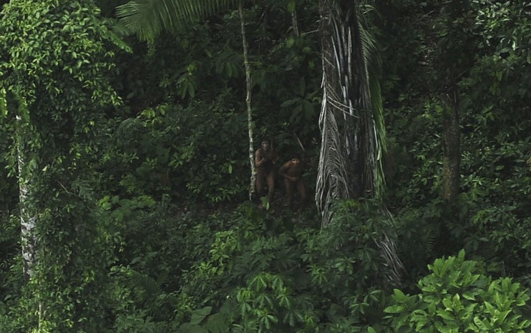 Indians who are considered uncontacted by anthropologists react to a plane flying over their community in the Amazon basin near the Xinane river in Brazil's Acre State, near the border with Peru. (REUTERS/Lunae Parracho)