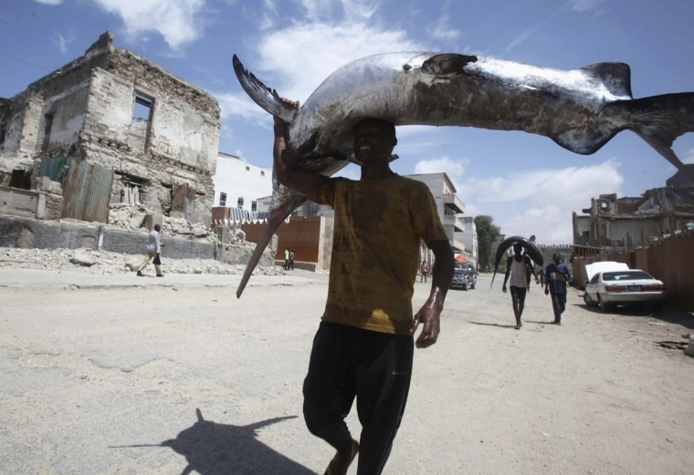 A fisherman carries a swordfish on his head from the Indian Ocean waters to the market in Somalia's capital Mogadishu on March 31, 2014. (REUTERS/Ismail Taxta)