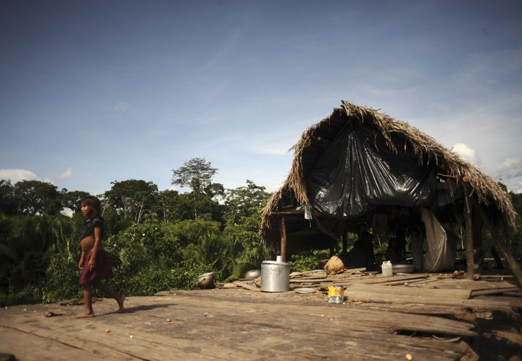 A Madija Indian child walks from one of the village huts which is a frequent target of raids by uncontacted Indians in the village of Dsama, along the Envira river in Brazil's northwestern Acre state. (REUTERS/Lunae Parracho)