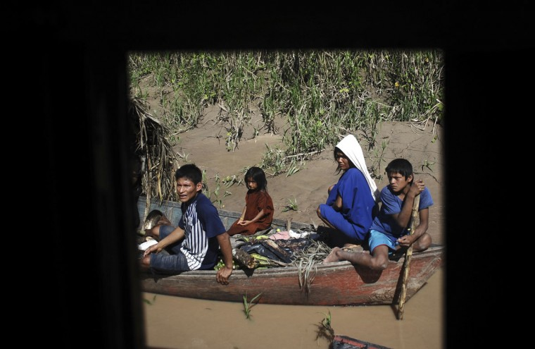 An Ashaninka Indian family navigates the Envira river towards the town of Feijo in search of medical care for a sick child, in Brazil's northwestern Acre state. (REUTERS/Lunae Parracho)