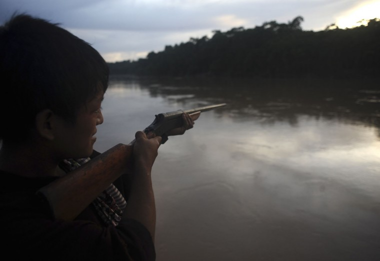 An Ashaninka Indian points his rifle across the Envira river on the grounds of a former government base called the Envira Front of Ethno-environmental Protection in Brazil's northwestern Acre state. (REUTERS/Lunae Parracho)
