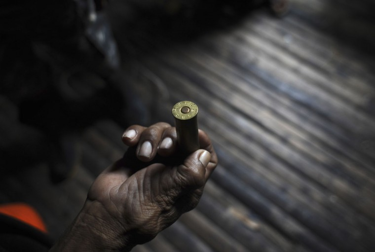 An Ashaninka Indian holds a shotgun cartridge he found on the grounds of the former government base called the Envira Front of Ethno-environmental Protection along the Envira river in Brazil's northwestern Acre state. (REUTERS/Lunae Parracho)