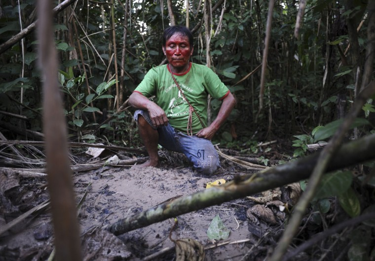 An Ashaninka Indian named Uarenco kneels over the grave of his niece who his family buried along the banks of the Envira river two weeks earlier when she died as they navigated the river in search of medical help for her diarrhoea, in Brazil's northwestern Acre state. (REUTERS/Lunae Parracho)