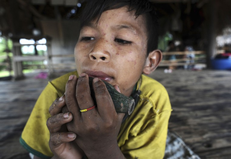 Binai, son of Cacique Omina of the Madija tribe, plays a ceramic flute made by uncontacted Indians which his father found and gave to him, in Igarape do Anjo in Brazil's northwestern Acre state. (REUTERS/Lunae Parracho)