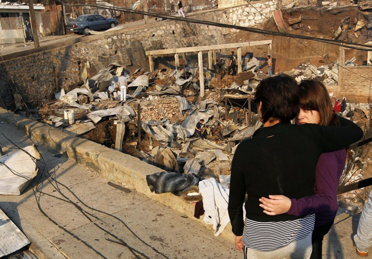 Residents survey the damage after a forest fire burned homes in Valparaiso. (REUTERS/Eliseo Fernandez)