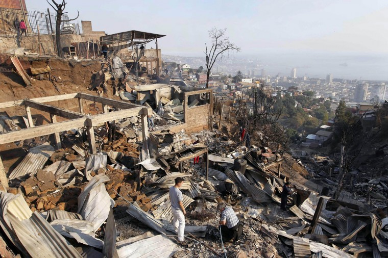 People walk amidst the remains of burnt houses after a forest fire in Valparaiso. (REUTERS/Eliseo Fernandez)