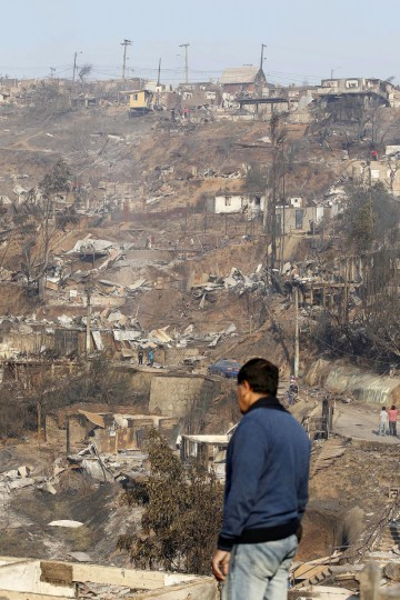 A resident surveys the damage after a forest fire burned homes in Valparaiso. (REUTERS/Eliseo Fernandez)