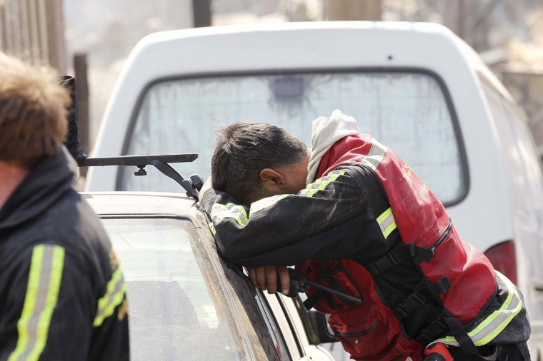 A rescue worker rests at the location where a forest fire burned several neighborhoods in the hills in Valparaiso. (REUTERS/Eliseo Fernandez)