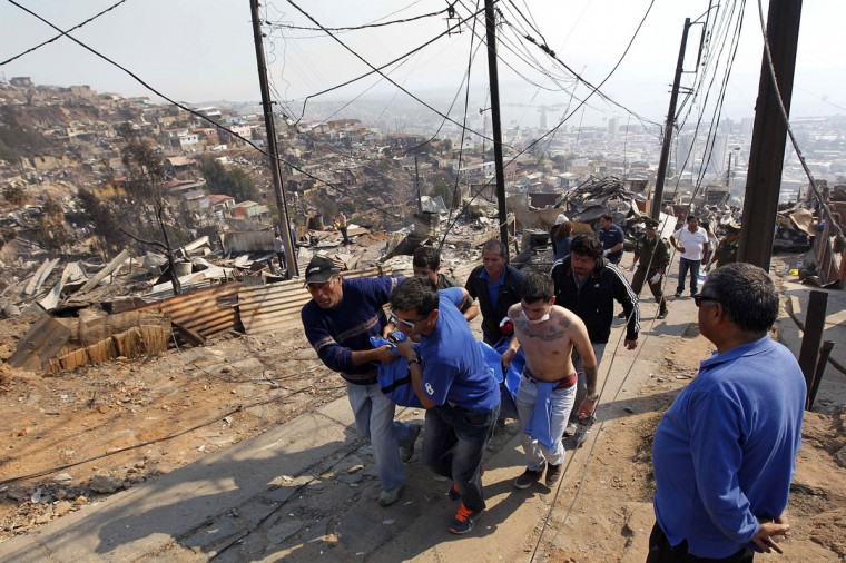 Residents and rescue workers carry a body from the place where a forest fire burned several neighborhoods in the hills in Valparaiso. (REUTERS/Eliseo Fernandez)