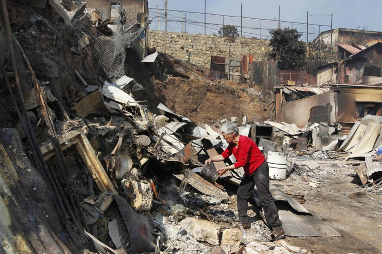 A resident works on the remains of a house after a forest fire burned several neighborhoods in the hills in Valparaiso. (REUTERS/Eliseo Fernandez)