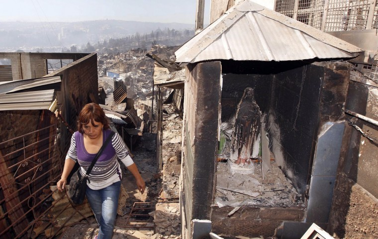 A resident walks past a religious image of the Virgin Mary after a forest fire burned several neighborhoods in the hills in Valparaiso. (REUTERS/Eliseo Fernandez)
