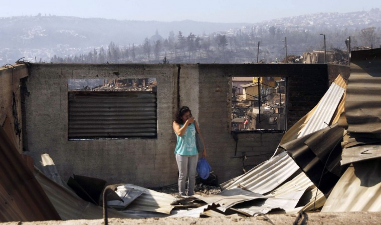 A resident reacts at the location where a forest fire burned several neighborhoods in the hills in Valparaiso. (REUTERS/Eliseo Fernandez)