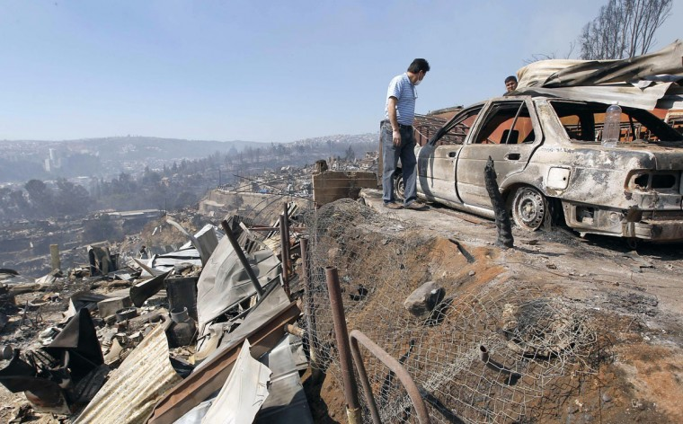 Residents inspect the remains of a car at the location where a forest fire burned several neighborhoods in the hills in Valparaiso. (REUTERS/Eliseo Fernandez)