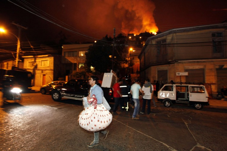Residents remove their belongings as a forest fire burns through several neighborhoods in the hills in Valparaiso. (REUTERS/Cesar Pincheira)