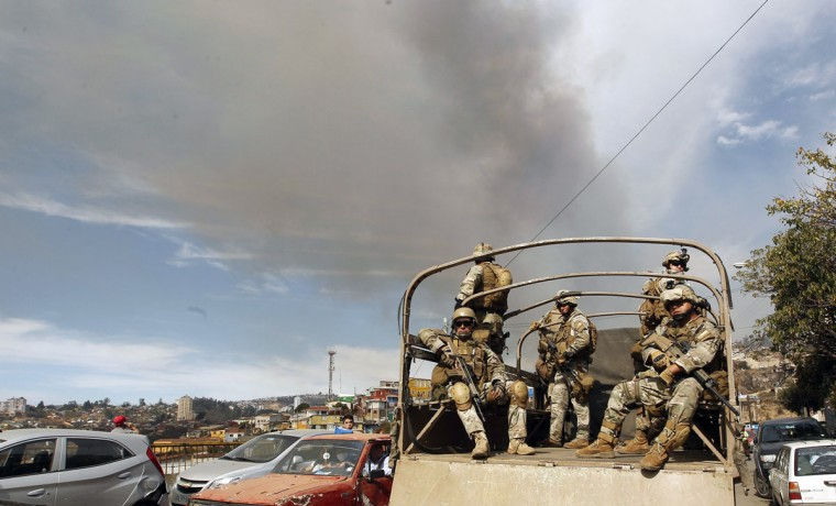 Soldiers in a truck patrol the location where a forest fire burned several neighborhoods in the hills in Valparaiso. (REUTERS/Eliseo Fernandez)