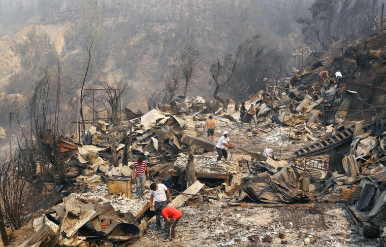 Residents survey the damage and remove the remnants of a house at the location where a forest fire burned several neighborhoods in the hills in Valparaiso. (REUTERS/Eliseo Fernandez)