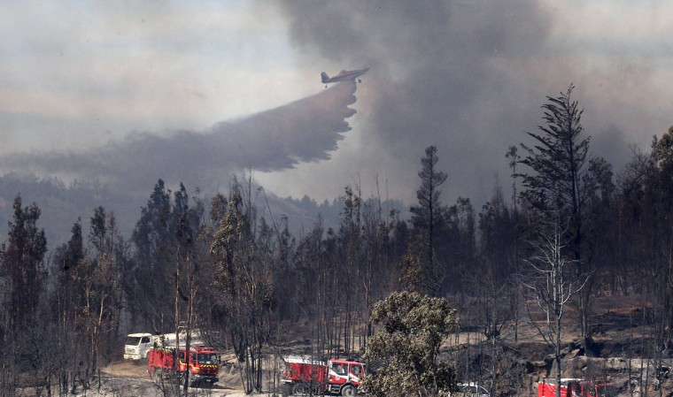A plane drops water on an area where a forest fire burned several neighborhoods in the hills in Valparaiso. (REUTERS/Eliseo Fernandez)