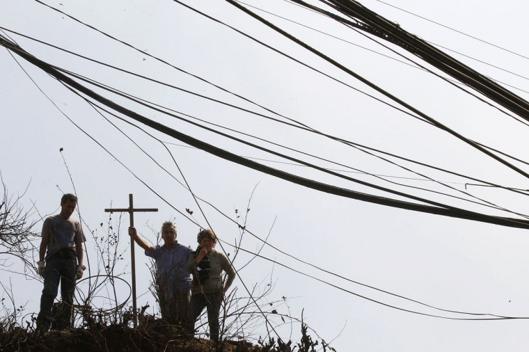 Residents stand next to a cross at the location where a forest fire burned several neighborhoods in the hills in Valparaiso. (REUTERS/Eliseo Fernandez)