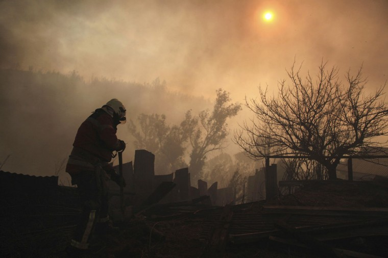 A firefighter removes the remains of a house at the location where a forest fire burned several neighborhoods in the hills in Valparaiso. (REUTERS/Cristobal Saavedra)