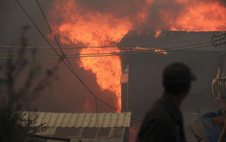 A fire burns a house at the location where a forest fire burned several neighborhoods in the hills in Valparaiso. (REUTERS/Cristobal Saavedra)