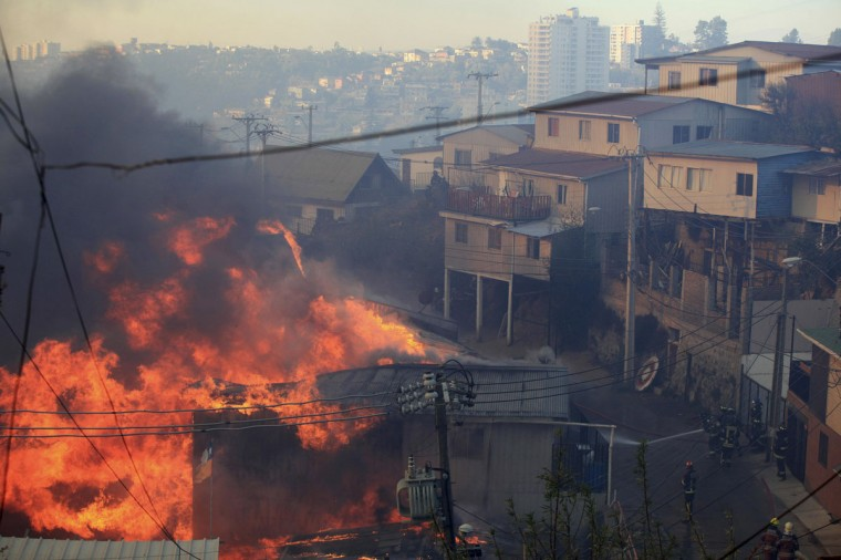 Firefighters try to put out a fire at the location where a forest fire burned several neighborhoods in the hills in Valparaiso. (REUTERS/Cristobal Saavedra)